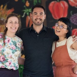 Joyce Liao, Meryn Corkery and Colin Dring stand smiling and arm-in-arm in front of a painted mural of vegetables.