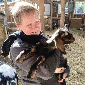 Janice Ammundsen cuddles one the baby goats on her Quadra Island farm. Photo: Rochelle Baker